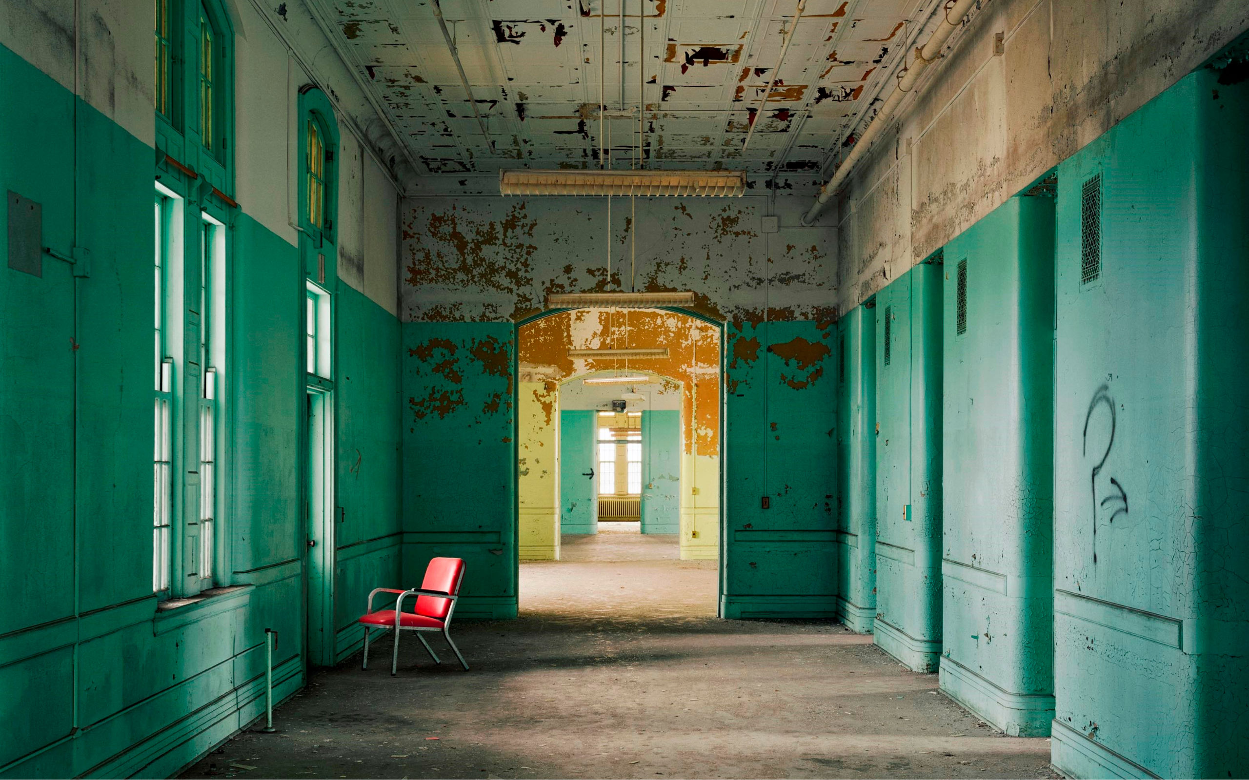 Derelict institutional hallway with peeling green paint and lone red chair in front of window.
