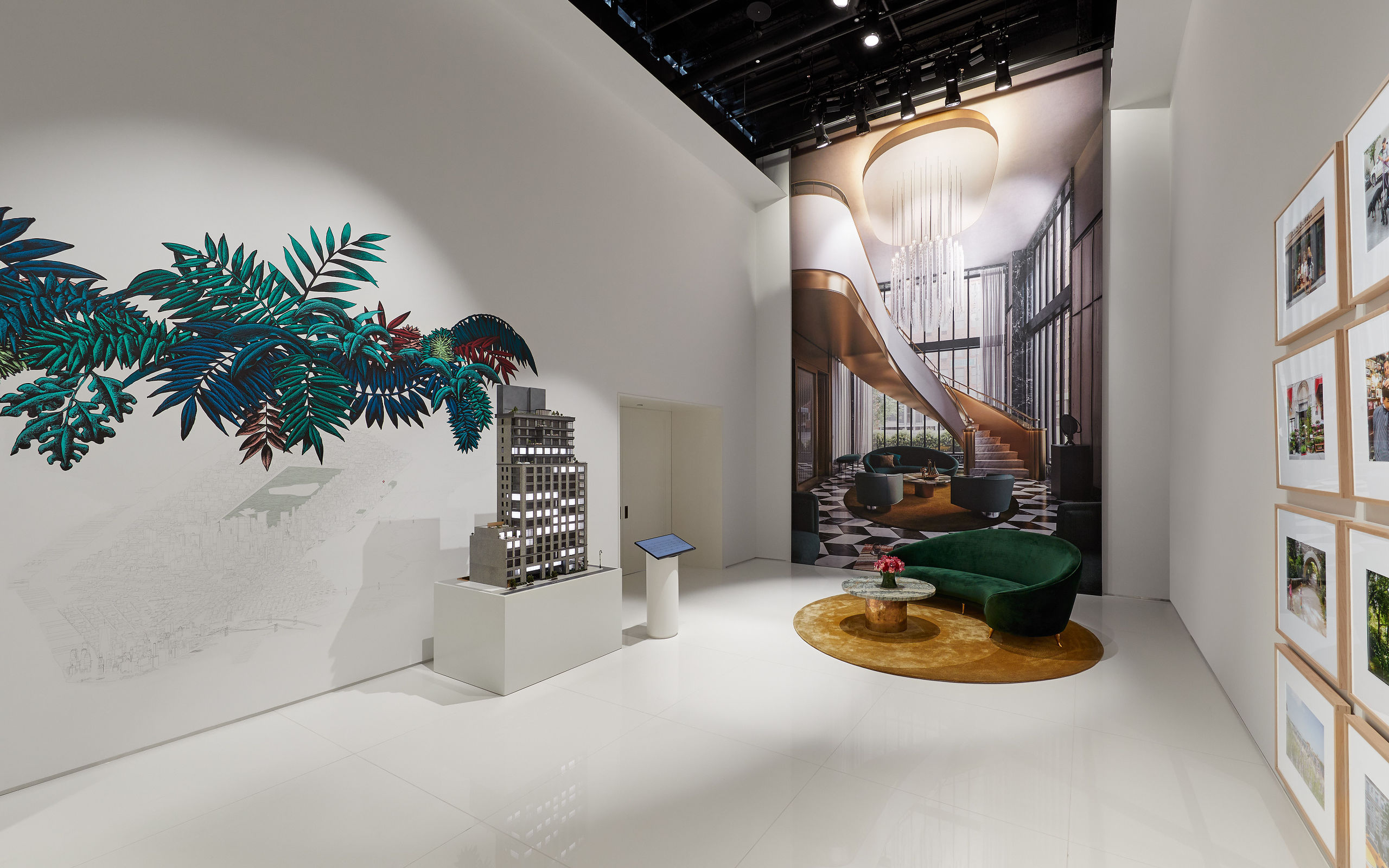 40 East End Avenue model showroom with artwork, large building renderings and model in front of green sofa.