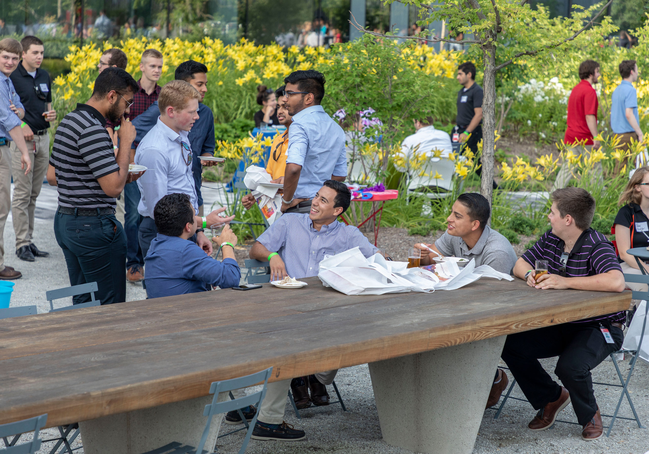 Group of young men sitting at outdoor table eating and drinking.