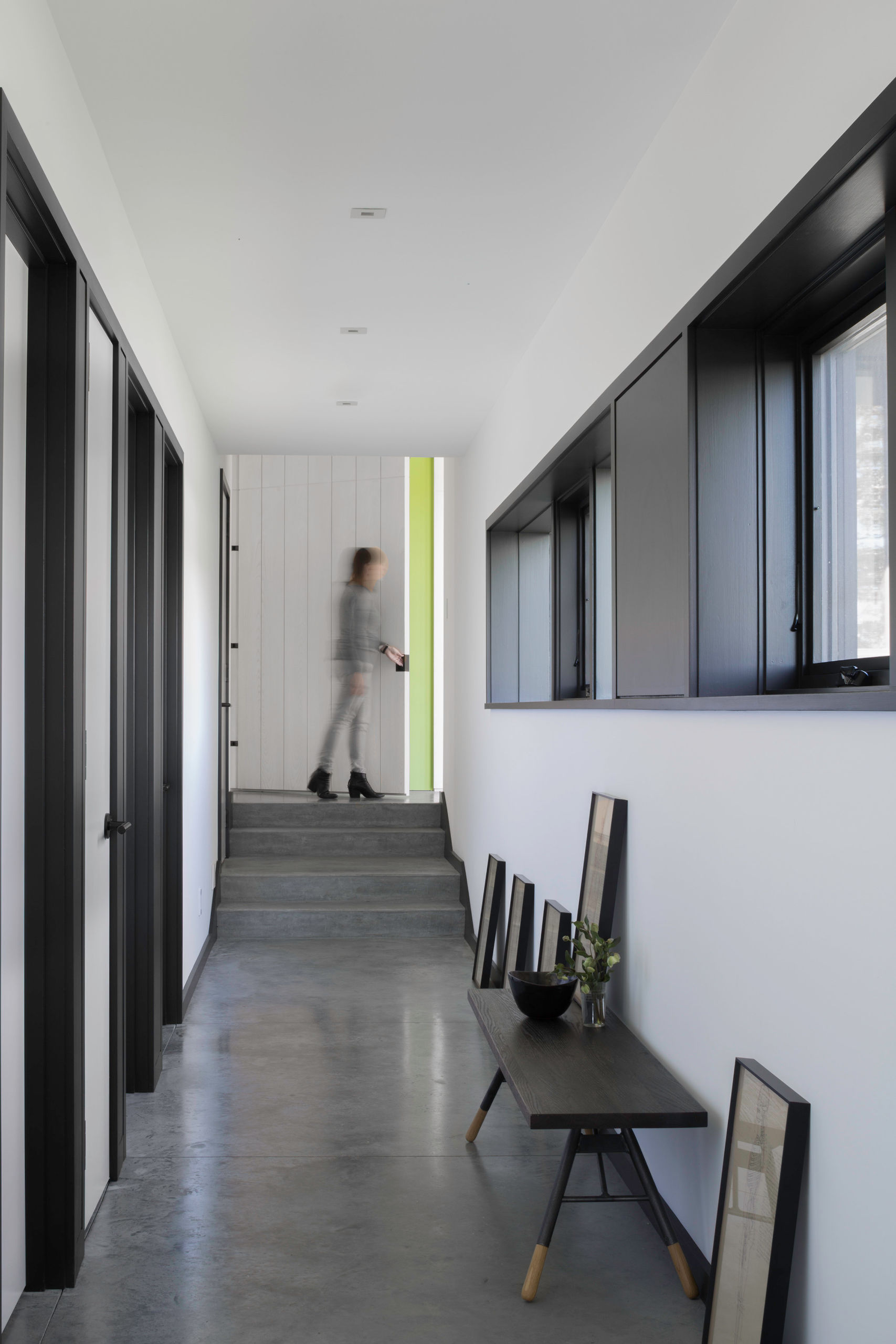 Looking down the hallway in the bedroom wing, with polished concrete floor and row of high windows along right side