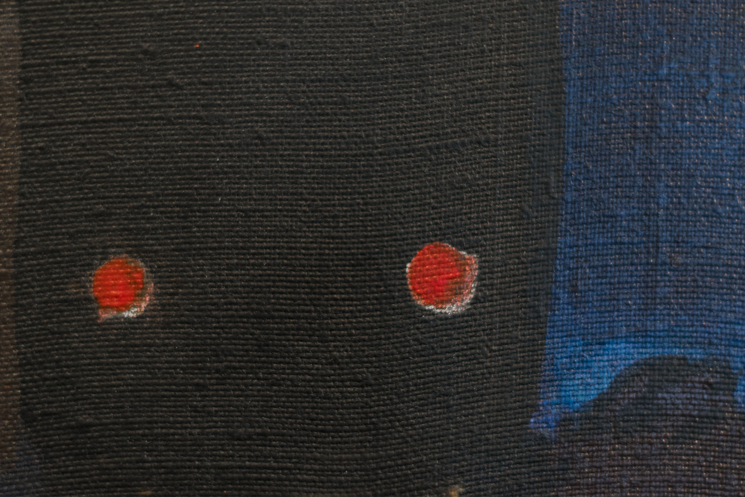 Close-up of painting showing black, blue and red tones.