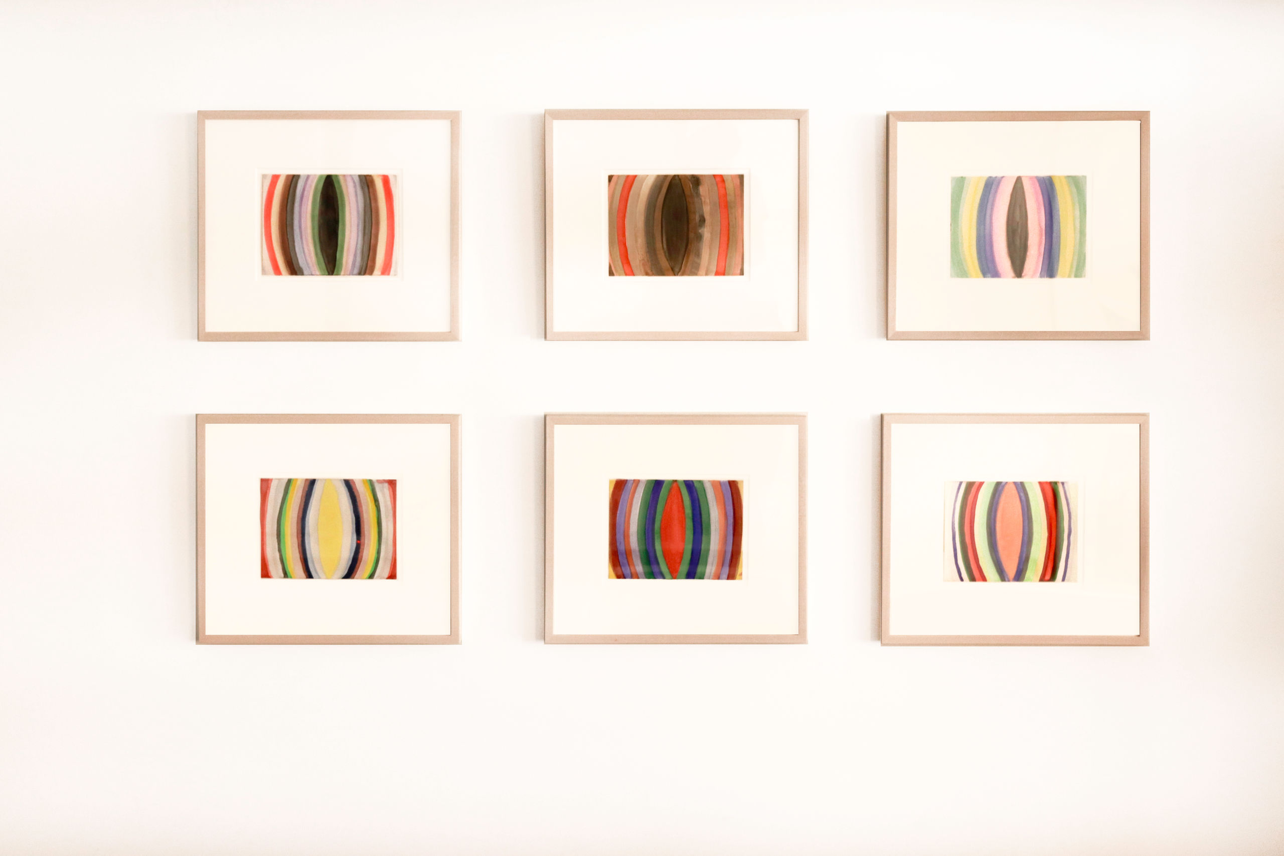 Six framed paintings on wall.