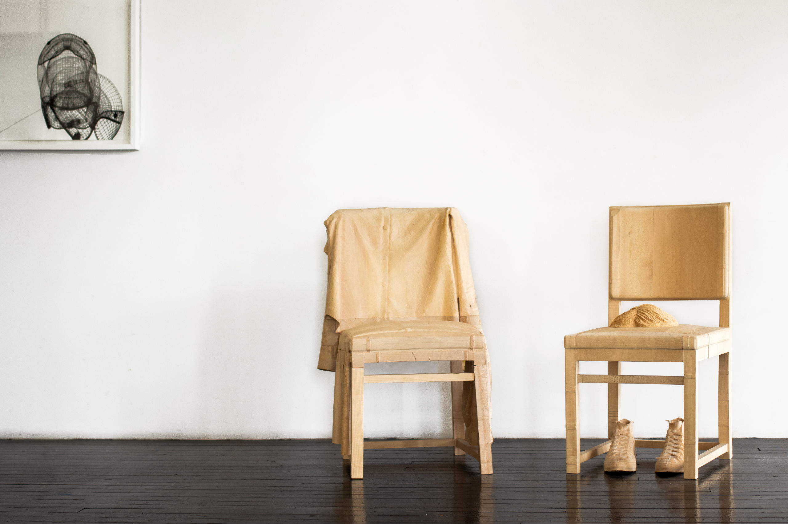 Wood sculpture of two chairs and shows next to black and white print, by Jonathan Brand.