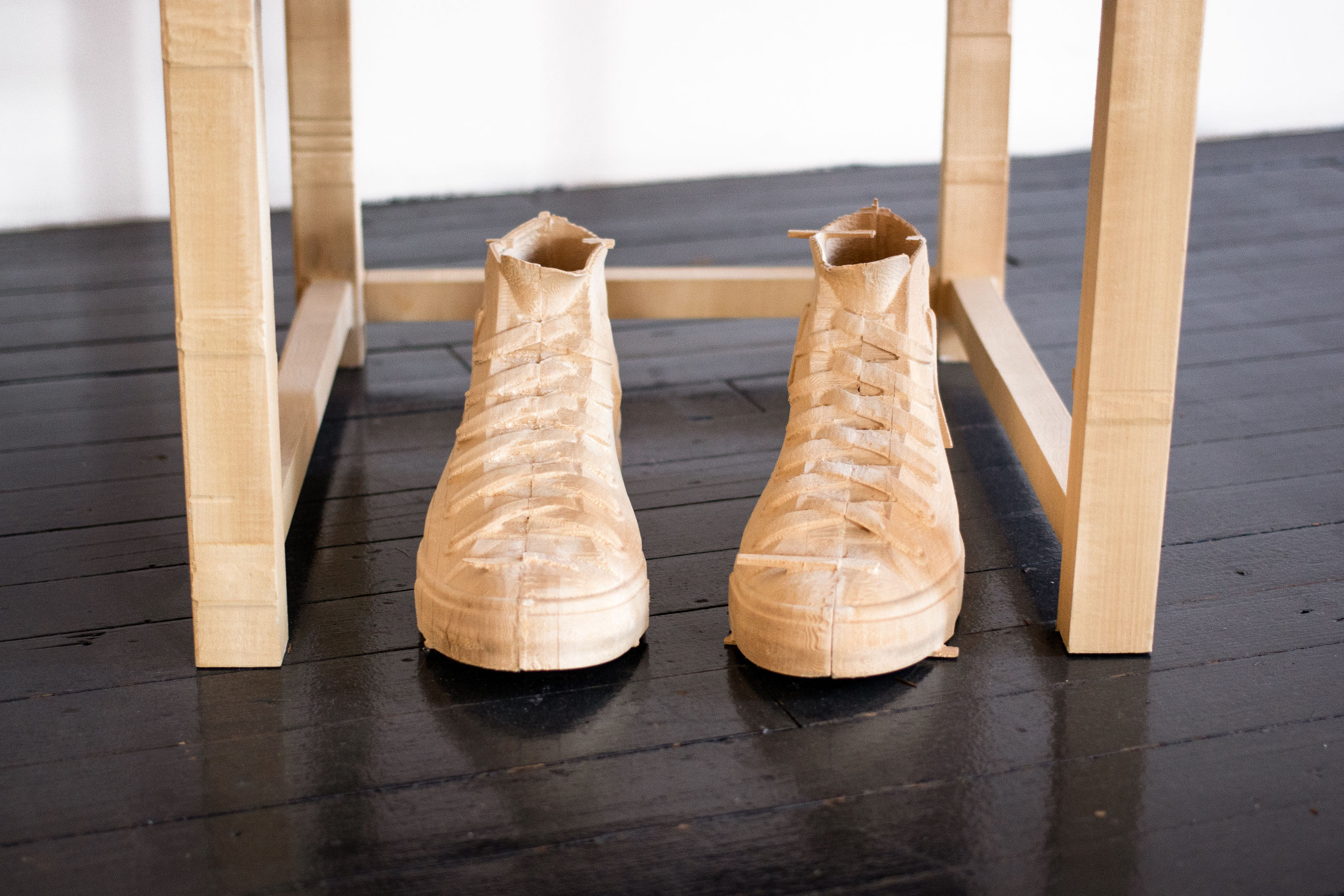 Wood sculpture of empty sneakers in front of a chair.