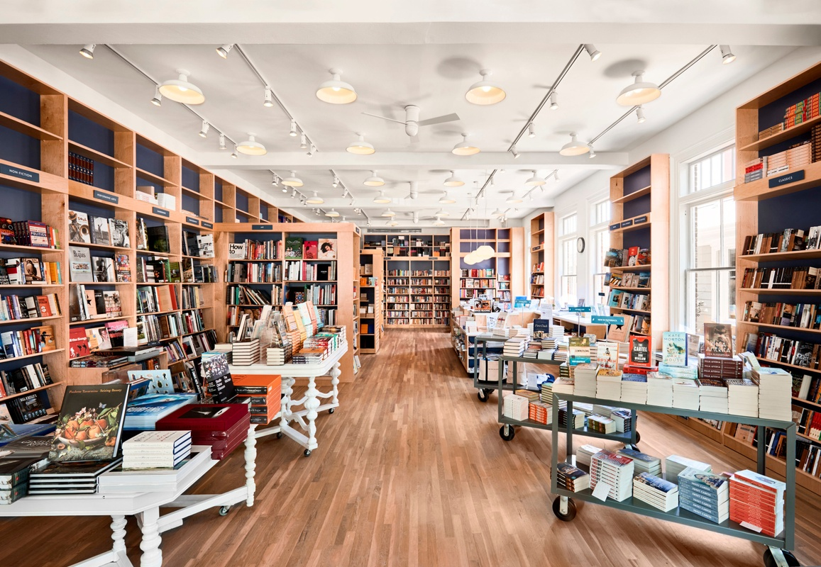 Bright bookstore with shelves full of books and display tables.