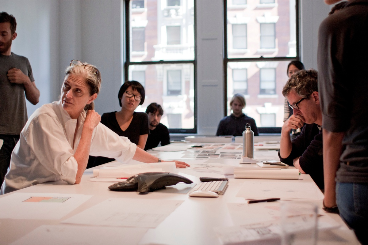 Design charette with table and DBP staff looking over drawings.